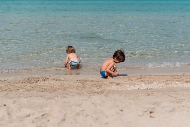 Totale von kindern, die am strand spielen