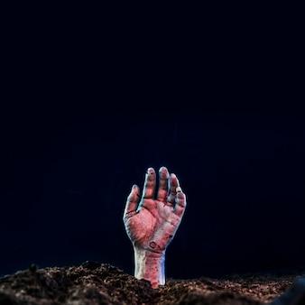 Tote hand, die vom boden hervorsteht