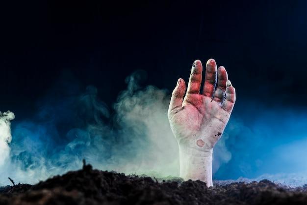 Tote hand, die vom boden im nebel hervorsteht