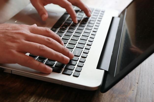 Touch screen der frauen und schreibender laptop des mannes auf hölzerner tabelle