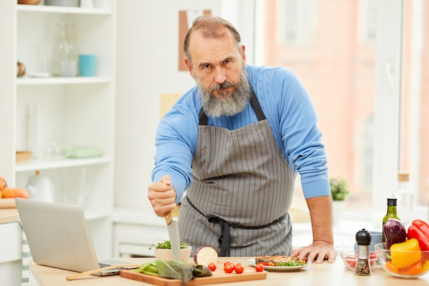 Tough senior man cooking