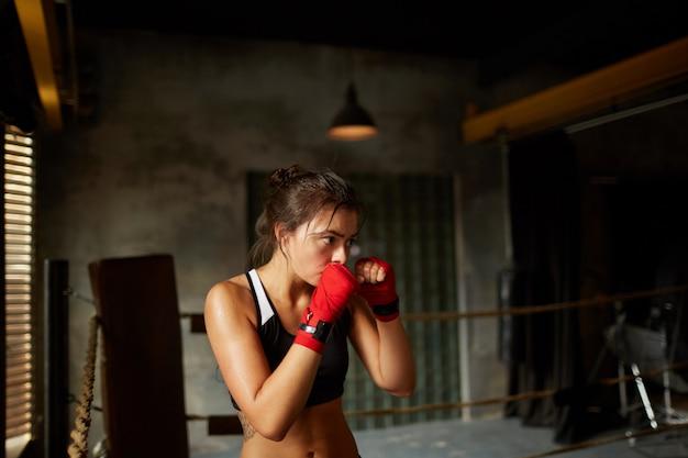 Tough young woman training im boxring