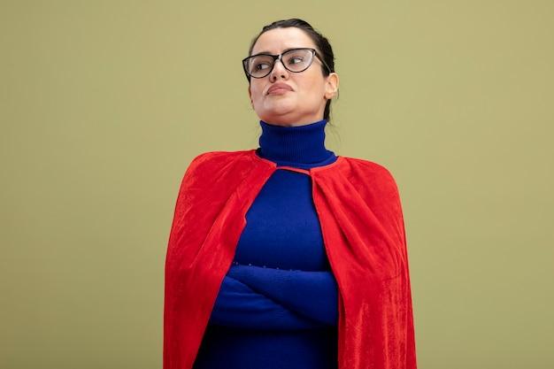 Toughtful junges superheldenmädchen, das seite betrachtet, die brillen kreuzt, die hände lokalisiert auf olivgrün