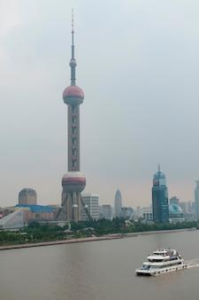 Tourboat mit dem orientalischen perlen-turm im hintergrund, pudong, shanghai, china