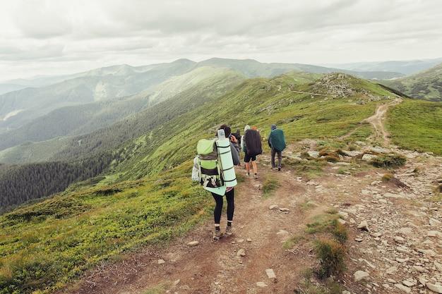 Tourismus, berge, lifestyle, natur, menschenkonzept - eine gruppe von wanderern mit rucksäcken geht auf einem weg zu einem bergrücken. backpacker-stil. konzept der aktiven freizeitgestaltung..