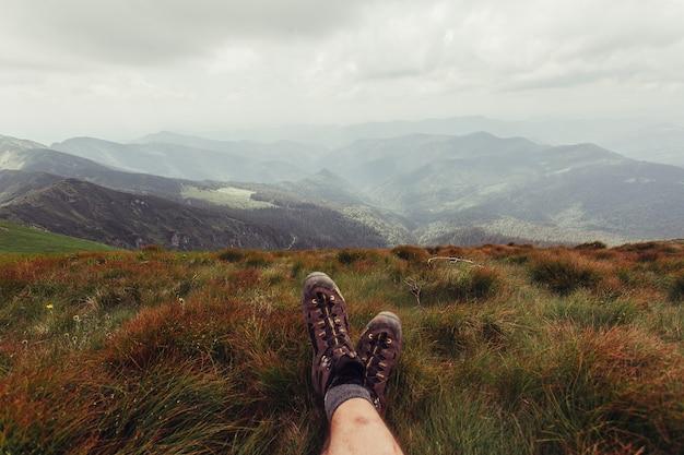 Tourismus, berge, lifestyle, natur, menschenkonzept - männerbeine in den braunen schuhen, die auf dem berg auf dem meereslandschaftshintergrund liegen
