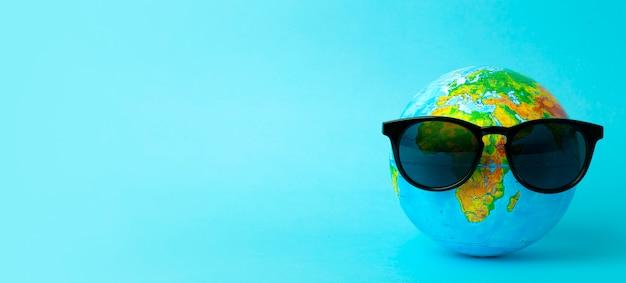 Tourismus-, ökologie-, ferien- und globalismuskonzept. kugel in der sonnenbrille auf einer blauen hintergrundfahne. minimal kreativ