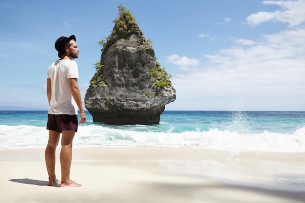 Tourismus-, reise- und urlaubskonzept. junges kaukasisches männliches modell, das schwarzen hut und freizeitkleidung trägt, die barfuß auf nassem sand mit felsiger insel vor ihm aufwirft, während große wellen ufer schlagen