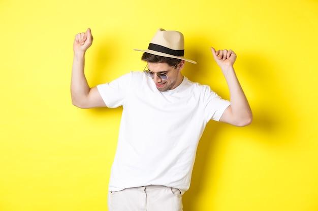 Tourismus-, reise- und urlaubskonzept. man tourist genießt urlaub, tanzt in strohhut und sonnenbrille, posiert gegen gelben hintergrund.