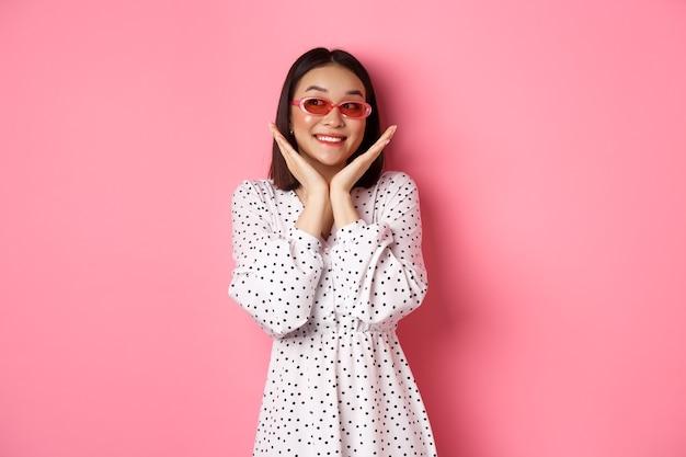 Tourismus- und lifestyle-konzept schöne asiatische frau, die ihr sauberes süßes gesicht mit sonnenbrille zeigt ...