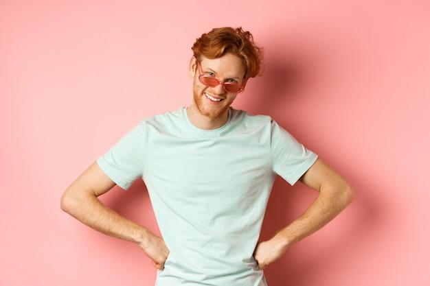 Tourismus- und urlaubskonzept lustiger bärtiger mann mit roten haaren, der eine brille trägt und lächelt und schaut...