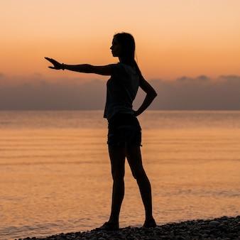Tourist bei sonnenaufgang macht übungen