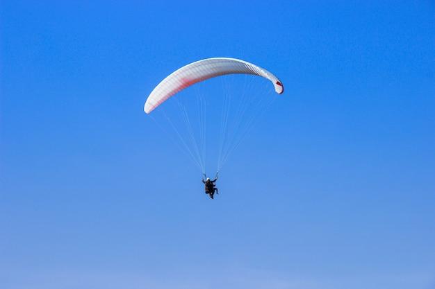 Tourist, der an einem hellen tag auf einem gleitschirm in den blauen himmel fliegt