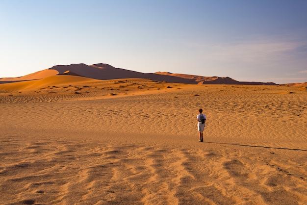 Tourist, der auf die sanddünen bei sossusvlei, namibische wüste, nationalpark namib naukluft, namibia geht.