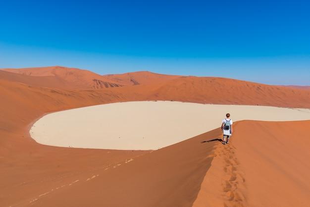 Tourist, der auf die szenischen dünen von sossusvlei geht