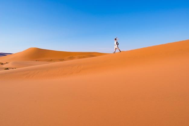 Tourist, der auf die szenischen dünen von sossusvlei, namibische wüste, namibia geht. abenteuer und erkundung in afrika.