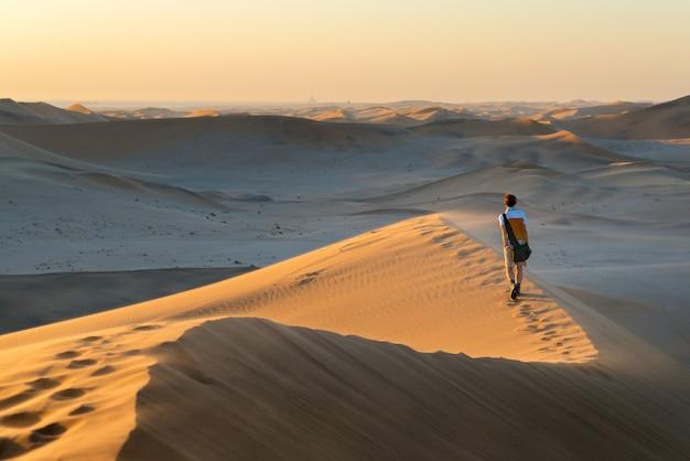Tourist, der auf die szenischen dünen von sossusvlei, namibische wüste, namibia geht.