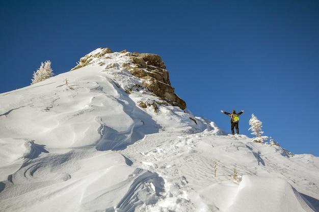 Tourist, der auf schneebedecktem berggipfel in siegerhaltung mit erhobenen händen steht, die ansicht und leistung am hellen sonnigen wintertag genießen.