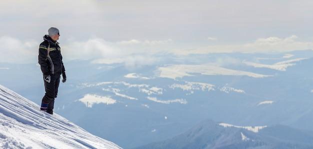 Tourist, der auf schneebedeckter bergspitze steht, die ansicht und leistung am hellen sonnigen wintertag genießt.