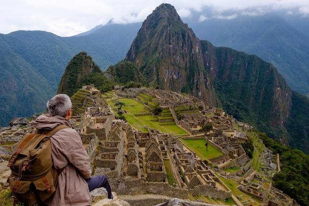 Tourist, der auf seinem zurück aufpassenden machu picchu lost city von inka, peru sitzt. eines der neuen sieben weltwunder.