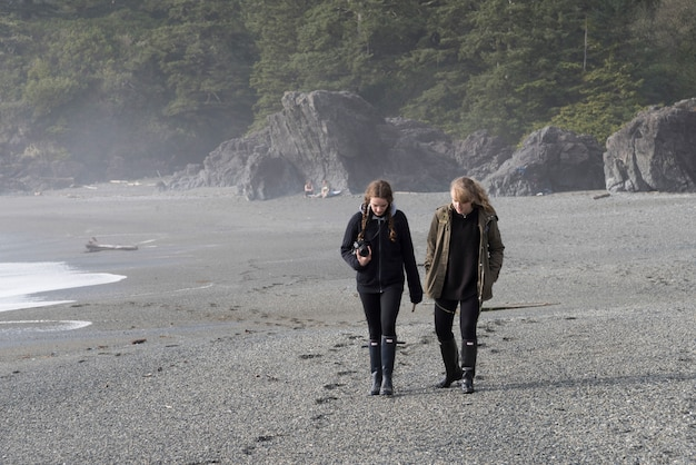Tourist, der auf strand, pazifische rand-nationalpark-reserve, tofino, vancouver island, britisches colum geht