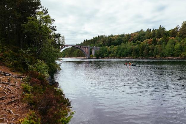 Tourist, der das boot auf dem see mit grüner landschaft rudert