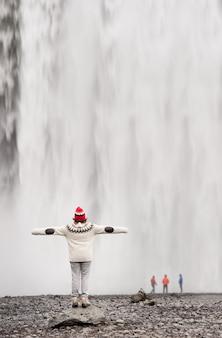 Tourist, der den skogafoss-wasserfall in island genießt