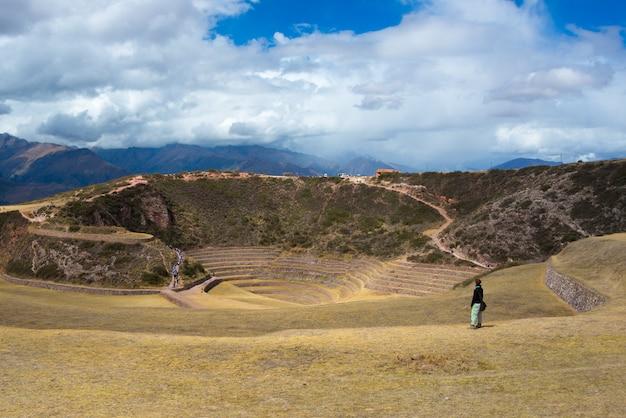 Tourist, der die archäologische fundstätte bei moray, reiseziel in cusco-region und im heiligen tal, peru erforscht. majestätische konzentrische terrassen, angeblich inkas labor für lebensmittelanbau.