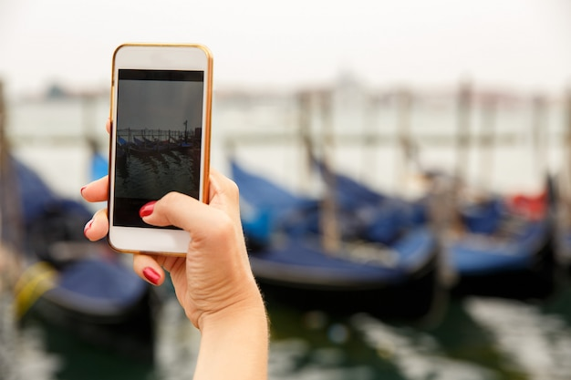 Tourist, der foto auf smartphone von gondeln auf wasser nimmt