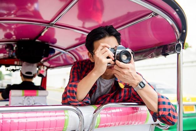 Tourist, der foto beim reisen auf taxi tuk tuk in bangkok thailand macht