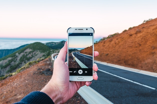Tourist, der foto der straße von seinem mobile macht