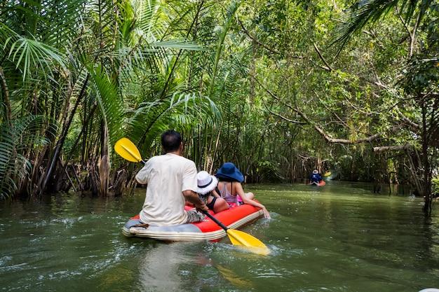 Tourist, der im kanal am wald in phangnga, thailand kayak fährt