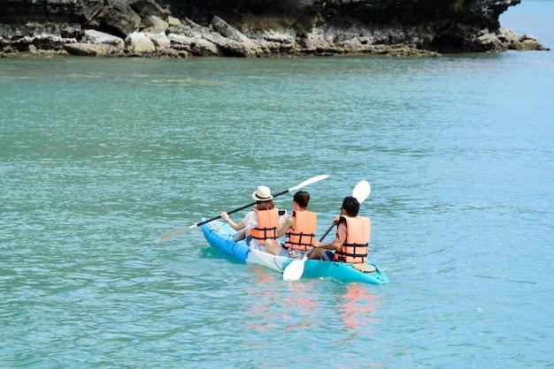 Tourist, der im thailändischen ozean von der rückwärtigen ansicht kayak fährt