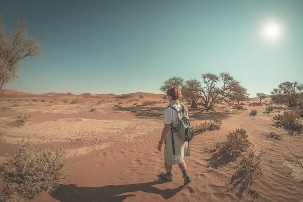 Tourist, der in die majestätische namibische wüste, sossusvlei, reiseziel in namibia geht.