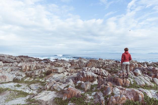 Tourist, der mit binokularem auf der felsigen küstenlinie de kelders, südafrika betrachtet, berühmt für das walaufpassen.