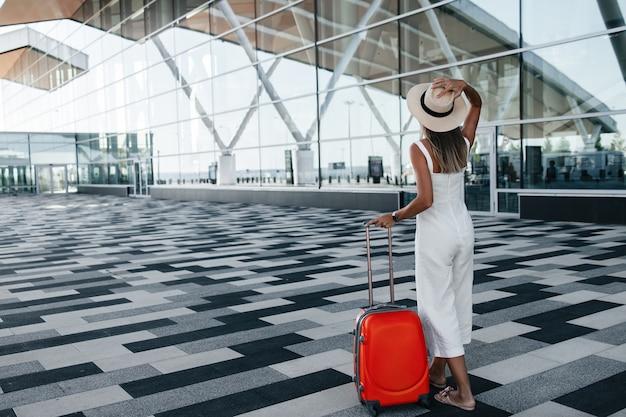 Tourist, der mit gepäck nahe flughafen steht