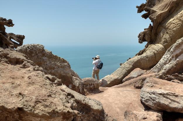 Tourist, der natur fotografiert, am rande der klippe stehend, iranische insel von hormuz, hormozgan, iran.