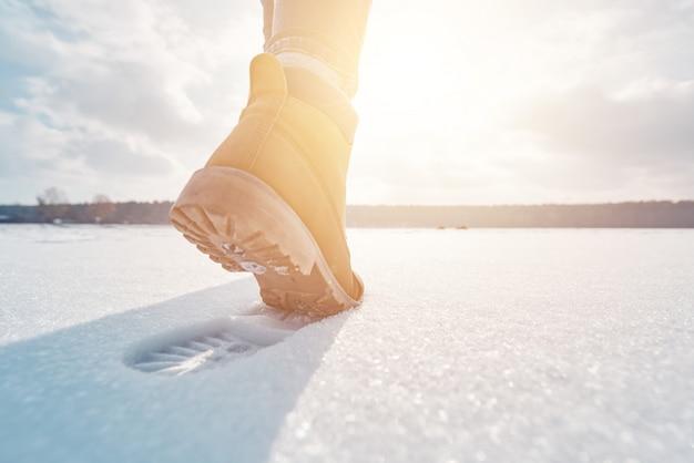 Tourist, der weg durch den schnee im sonnenuntergang geht