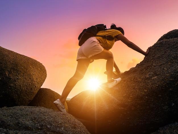 Tourist des jungen mädchens klettert zur spitze des felsens. frauenwanderer mit rucksack klettert steiles felsiges gelände.