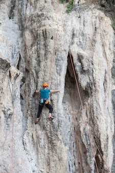 Tourist frau klettern auf einer kalksteinwand auf krabi provinz in thailand.