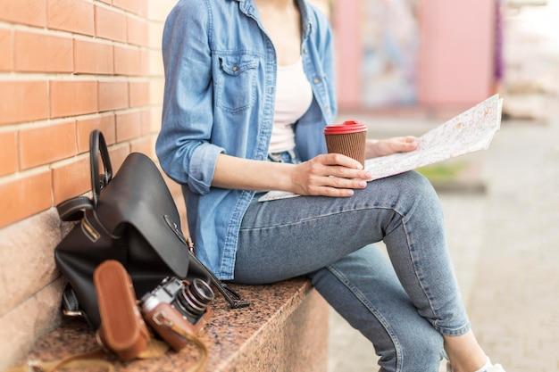 Tourist genießt kaffee beim überprüfen der karte