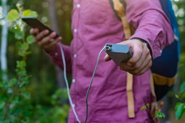 Tourist hält ein smartphone mit einem tragbaren ladegerät in den händen. mann mit powerbank lädt das telefon vor der kulisse von natur und wald auf.