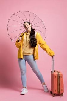 Tourist hält ihr gepäck und regenschirm