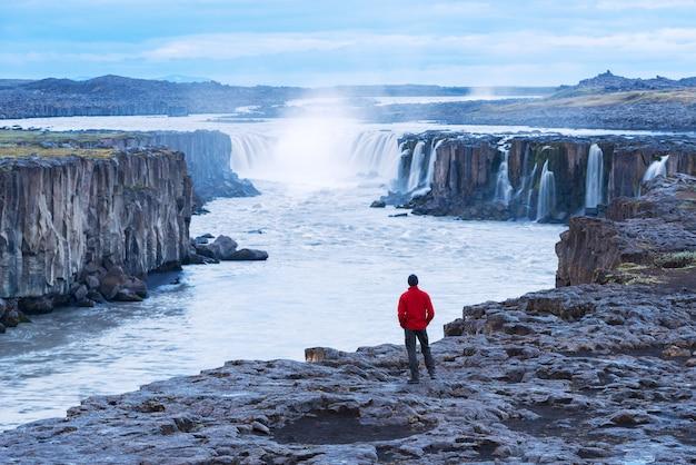 Tourist in einer roten jacke schaut auf den selfoss-wasserfall