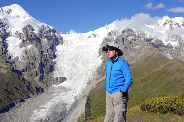 Tourist in gläsern steht auf einer oberfläche von berggletschern