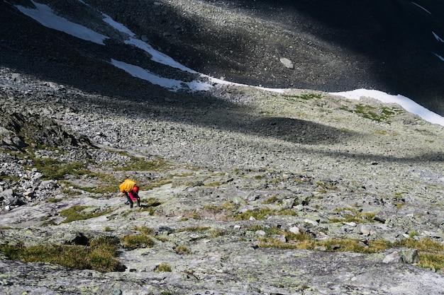 Tourist klettert die steine in den bergen hinauf. die felsige moräne hinauf