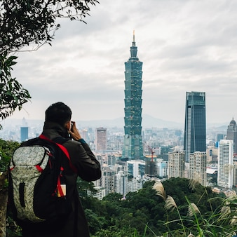 Tourist machen sie ein foto des luftpanoramas über im stadtzentrum gelegenem taipeh mit wolkenkratzer taipehs 101 in der dämmerung.