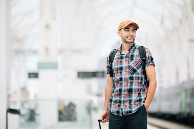 Tourist man backpacker und koffer zum reisen am bahnhof