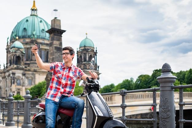 Tourist mann, selfie während der sightseeing-tour mit der vespa in berlin