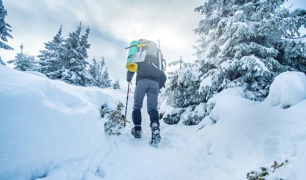 Tourist mit ausrüstung, die im winter schneebedeckten berg klettert